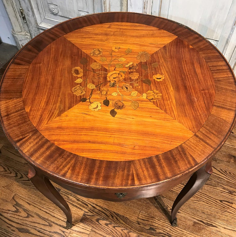 Wonderful quality 19th century French Transitional kingwood table. The circular top with mahogany banding and possessing fine satinwood, tulip wood, and olive wood floral inlays. Fitted with a shaped drawer accented with a fancy bronze escutcheon.
