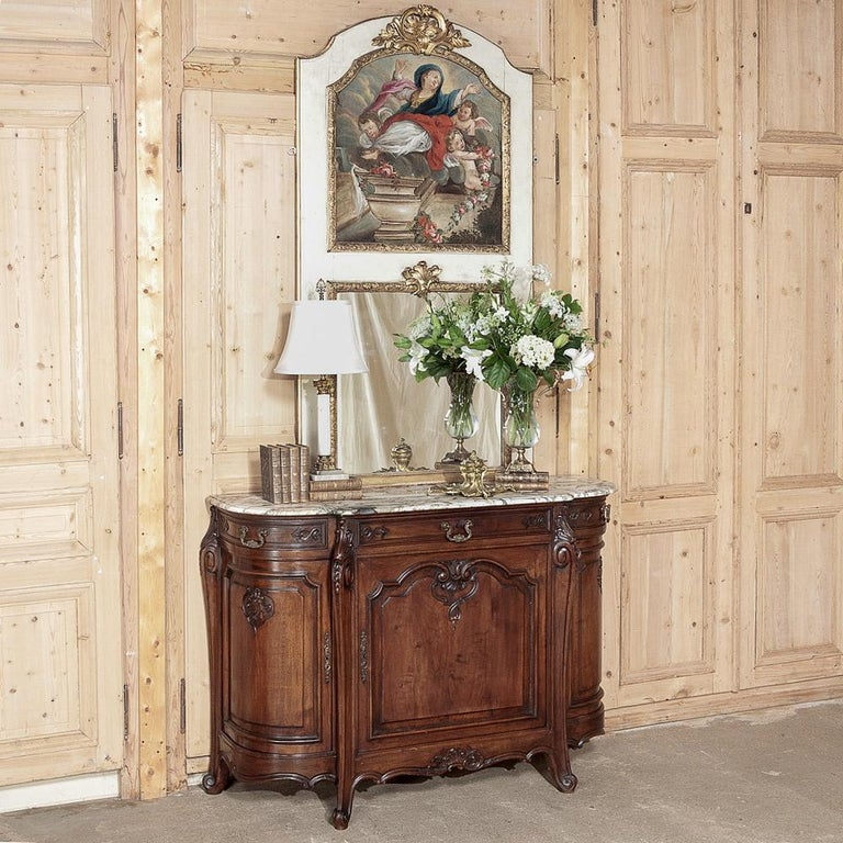 19th century French Trumeau with hand painted Madonna, featuring an uncommon arched crown on the frame of this gorgeous trumeau and gilded molding around the mirror below. The exceptional painting of the Assumption of The Madonna attended by angels