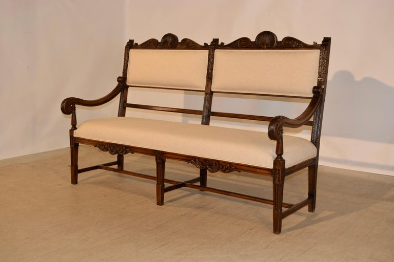 19th century upholstered bench from France made from oak with newly upholstered seat and back. The frame is ornately hand carved and has shell and leaf patterns with hand carved scrolled arms and supported on hand-turned legs joined by simple