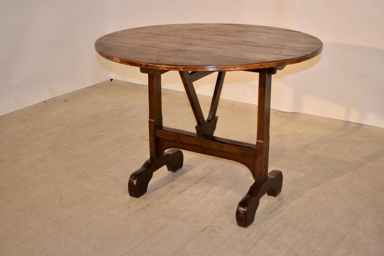 19th century French vendange table with a pine top following down to an oak base. It has a trestle base with an ingenious and simple mechanism for the tilt top. It is supported on wonderfully proportioned feet. The table down measures 39.5 x 38.13 x