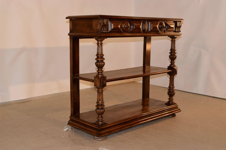 19th century French walnut buffet with a banded top which also has a beveled edge. This follows down to two paneled drawers over two lower shelves. The shelf supports are wonderfully hand turned and carved in the front, and are simple in the back
