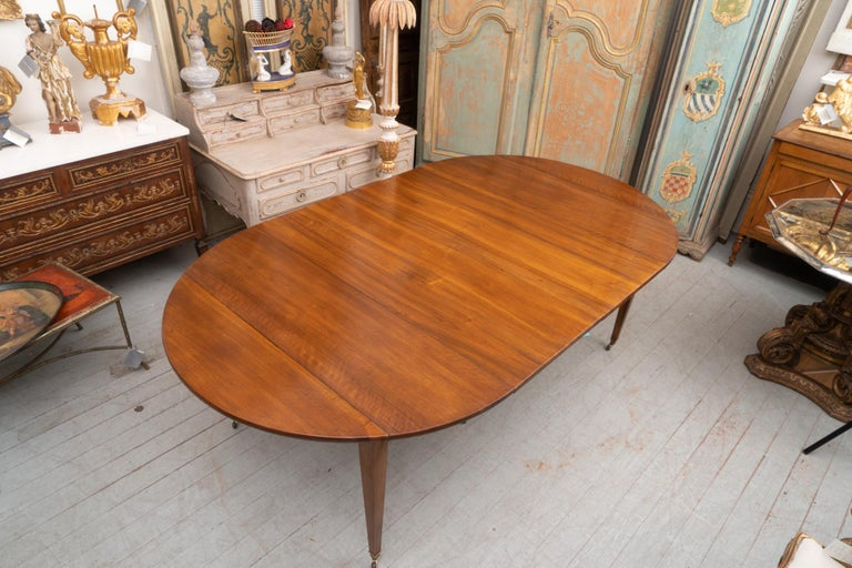 French walnut extension table with four finished leaves. The picture shows the table with two of the 20 inch leaves in place.