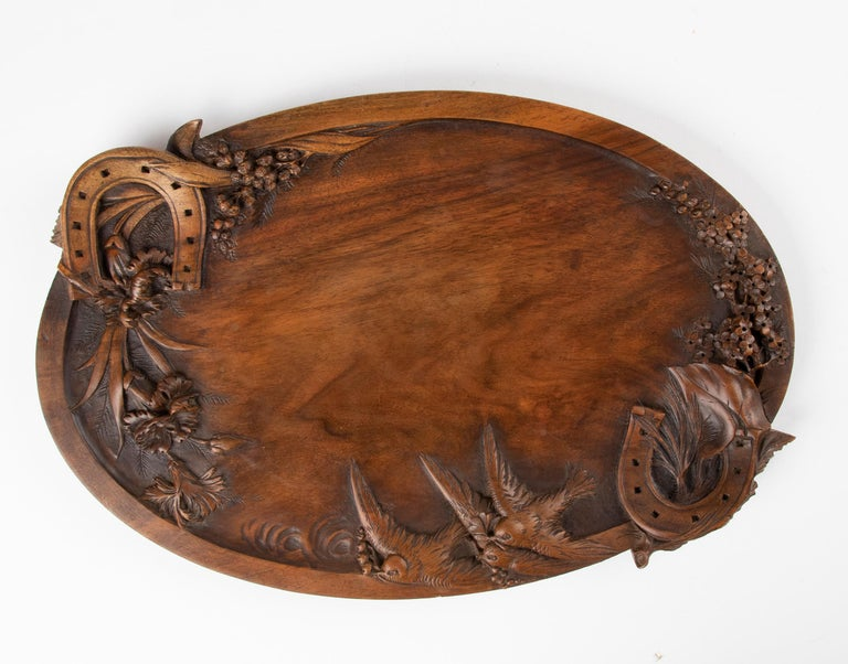 Beautiful antique tray with beautifully detailed carvings. The theme is so sweet, with the horseshoes symbolizing good luck and the swallows symbolizing love and freedom. This theme is common in French arts at the end of the 19th century. The wood