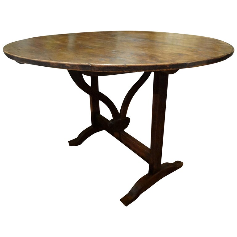 Offered is a 19th century French round walnut wine tasting table from the Burgundy Region of France. Our French wine table has a rotating stretcher and trestle which supports the tabletop when in use. This walnut wine table can be folded for