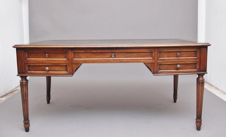 19th century French walnut writing table, the moulded edge top having a green leather writing surface decorated with gold and blind tooling, each end of the table having pull out slides, the front of the table there are a combination of four oak