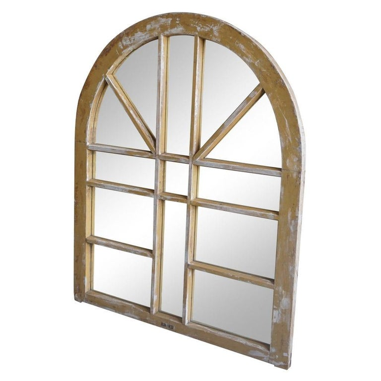 An antique French rustic Orangerie framed wall mirror with an arched sunburst top in wood, original mirror glass in good condition. Wear consistent with age and use, Circa 1880, Marseilles, France.