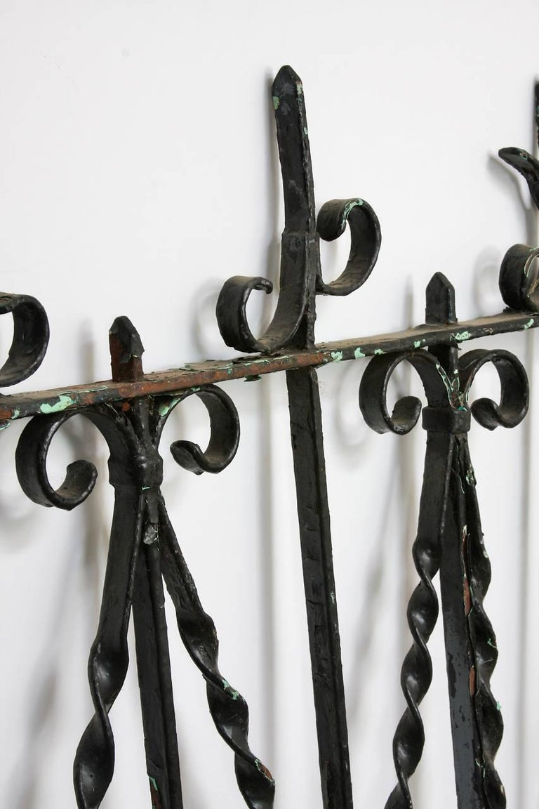 Rustic 19th century French fence railing fragment constructed from wrought iron. Beautifully handcrafted with twisted, scrolled decorations and heart motifs. The iron still retains much of the old lacquer finish in thick layers of black paint.