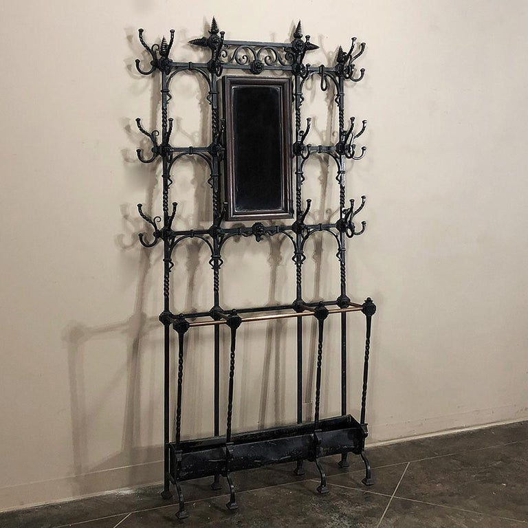 19th century French wrought iron hall tree is a marvel of the metalsmith's art! Intricate scrollwork, twisted rod, and spiral finials abound, with a wood framed mirror on gimbals and an umbrella stand below to keep the wetness under control. An