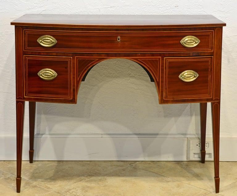 This superior Gerogian bowfront writing desk features a one piece polished satinwood stringed mahogany top above a body with a long drawer and two short deep drawers flanking a semi circular knee hole. The desk rest on four slightly splayed square