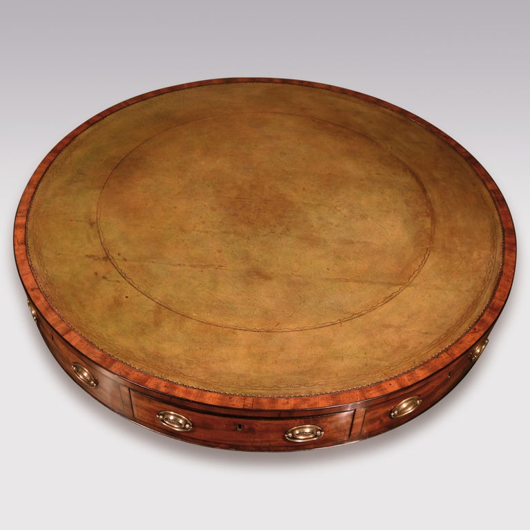 A George III period well-figured mahogany revolving drum table, ebony strung throughout, having green tooled leather circular top above frieze drawers supported on turned stem with reeded 4-splay legs ending on original brass castors.