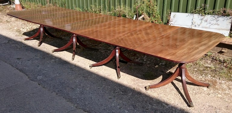 18th century mahogany antique dining table standing on four pedestals, each with four splay base. This is a wonderful table which has faded to a desirable golden brown honey color. The bases are strong and a generous shape and the top of each leg