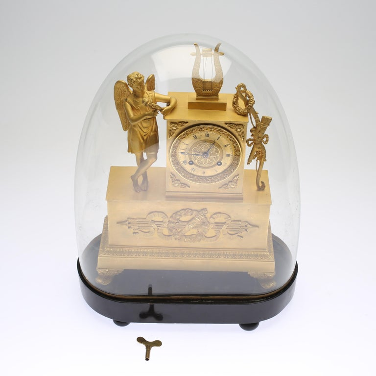 Early 19th century gilt brass mantle clock with the glass hood. Decor of foliage, arrows, and bow. Crowned by an angel with lyre. The glas dome has protected it beautifully and it is in beautiful condition for its age.