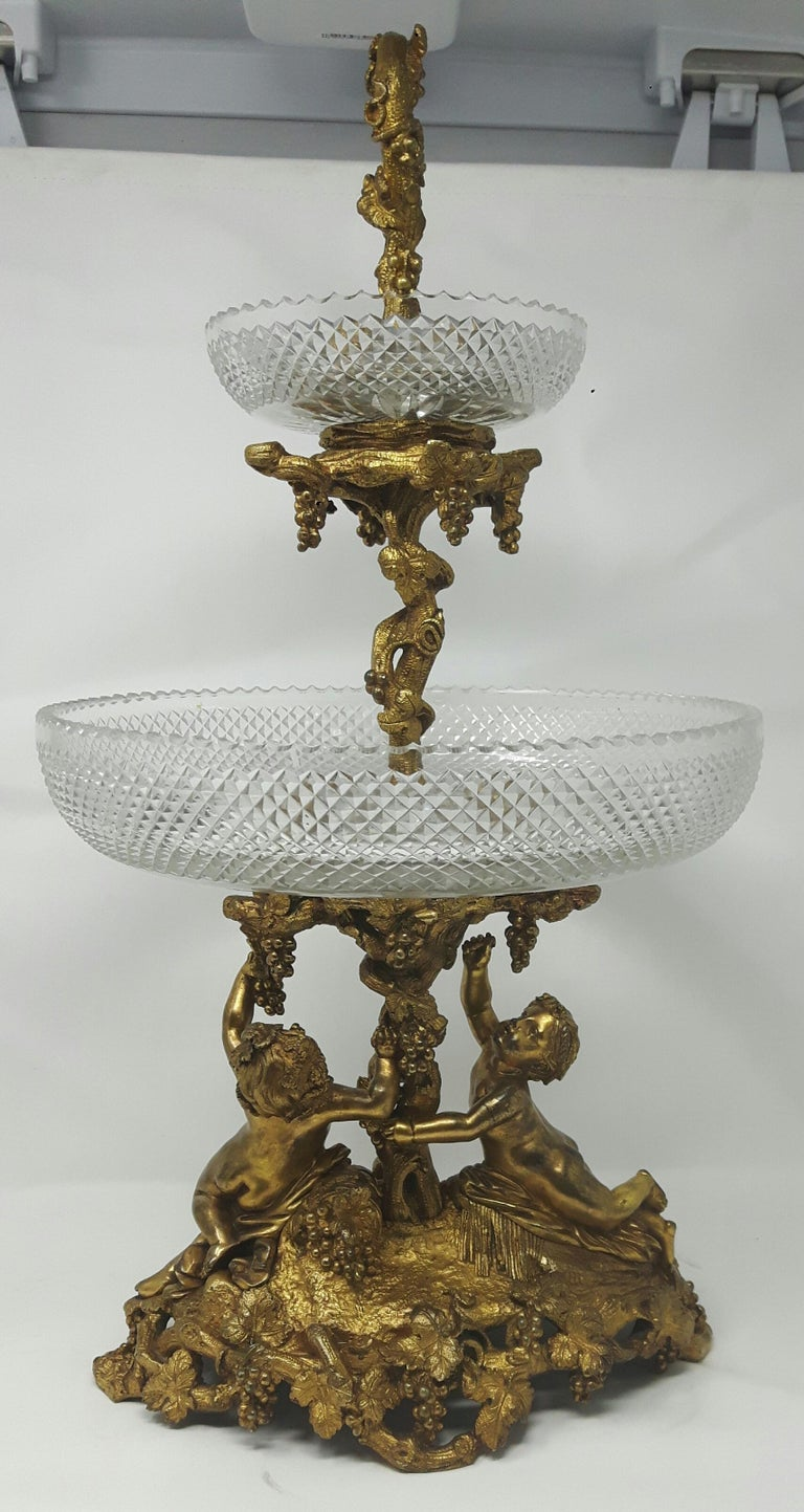 A gilt bronze centrepiece, with two crisply cut bowls on fruiting vine centre supported by two putti on oval base.