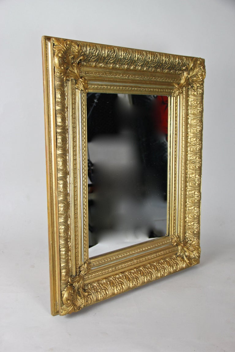 Palatially 19th century gilt Biedermeier wall mirror from the second period circa 1860 in Austria. With an age of nearly 160 years, this large antique mirror impresses with its massive frame showing an opulent designed surface with amazing stucco