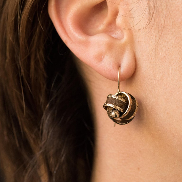 Earrings in 14 karats yellow gold. Consisting of a gold bow in which is woven a wick of braided brown hair, each earring is also centered around a golden pearl. The fastening system is a gooseneck. Height: 2.4 cm, widest width: 1.5 cm. Total weight
