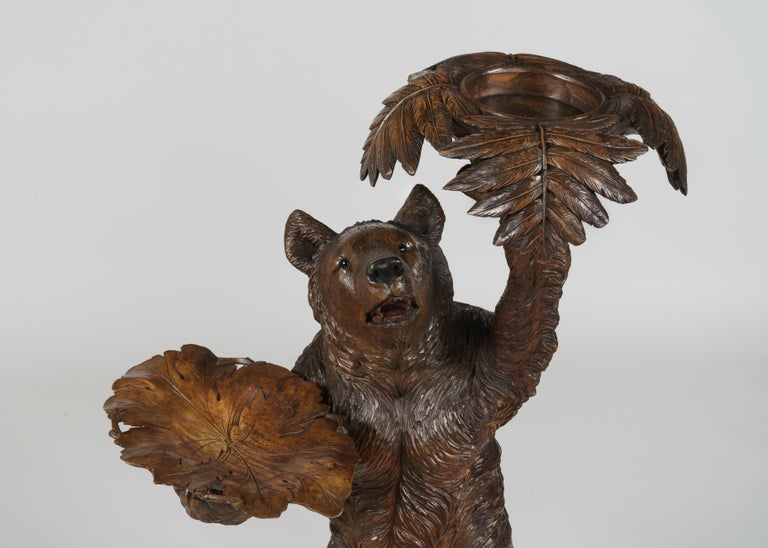 A 'Black Forest' bear jardinière Possibly by Jacob Trauffer  Constructed in a very well-patinated and carved lindenwood, the bear figure standing on an X-shaped outcrop, his right hand presenting a carved foliate tray, the left supporting a