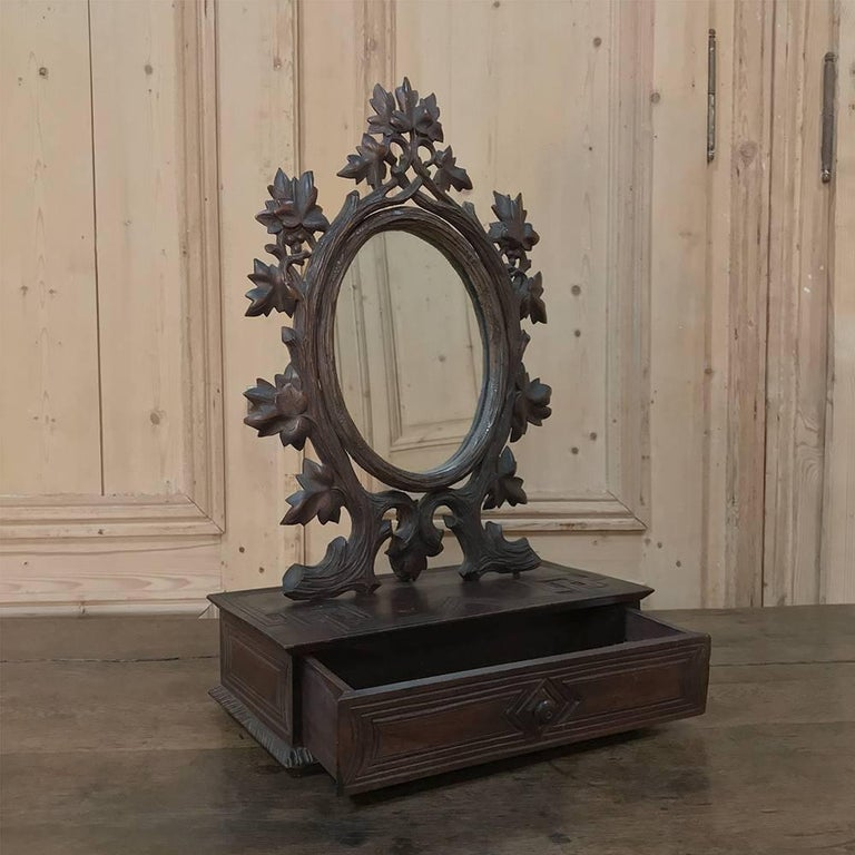 19th century hand-carved black forest vanity mirror-box was sculpted from solid fruitwood in the naturalistic form that is definitive of the region, appearing to be the flora that exists in the beautiful Alpine surroundings of the area. The oval