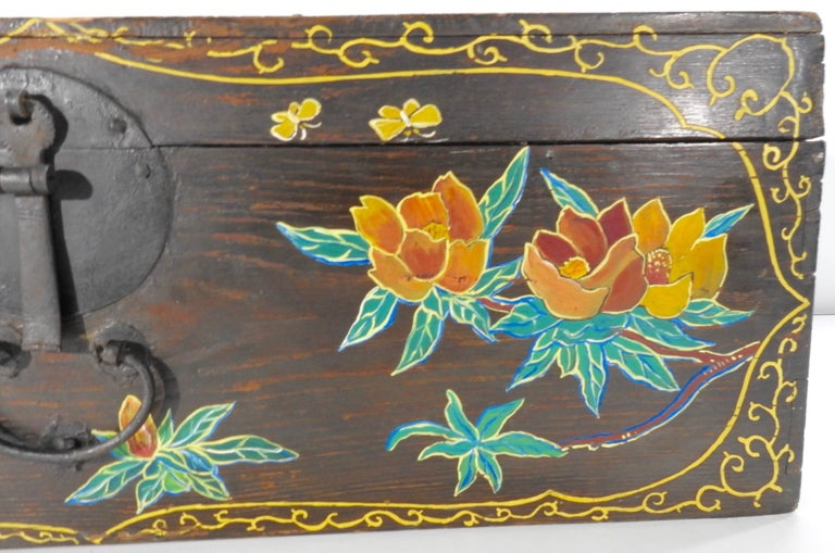 Birds and flowers embellish the front of this wooden trunk along with a scrolling border. Soft shades of yellow, orange and green make up the artwork and the painting appears to be a mid-20th century embellishment. A cast iron latch completes the