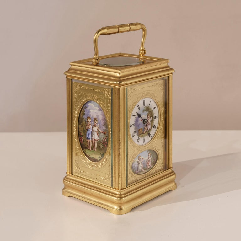 A fine carriage clock  The engraved gilt case rises from an ogee plinth, and is dressed with elliptical polychrome enameled plaques to the fascia and the sides, depicting children in a Romantic setting, with a carrying handle atop, set across the