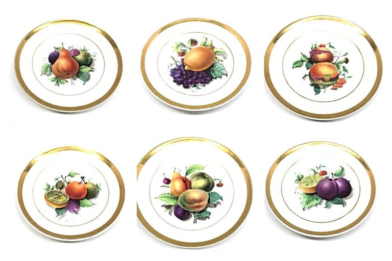 A set of six porcelain Fruit still life themed plates, made in Thuringia, Germany, circa 1860s.  Central images show a hand painted still life pattern of brightly colored fruits, encircled by banded rims in gold. This is a set of six different