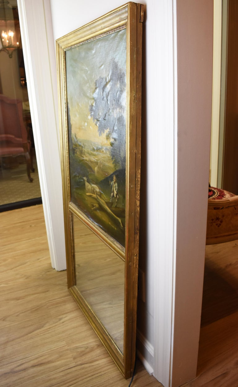This early 19th century hand-painted Trumeau Mirror features a lovely landscape scene. Both the mirror and the oil painting sit vertically in a simple giltwood frame. There has been some stretching to the canvas such that there are minor wrinkles as