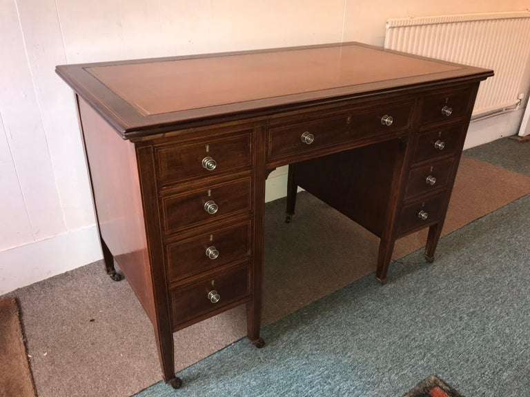 Hepplewhite style mahogany and boxwood inlaid one piece desk with nine deep drawers with brass knobs, ending on square tapered legs. This is a superior quality piece, even the side panels are inlaid. The gilt tooled leather top is in immaculate