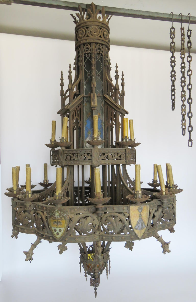 Huge hammered iron chandelier of great Gothic influence with painted crystal coat of arms set on intricate detailed ironwork with scrolls, foliage and dragons and stained glass windows. 
