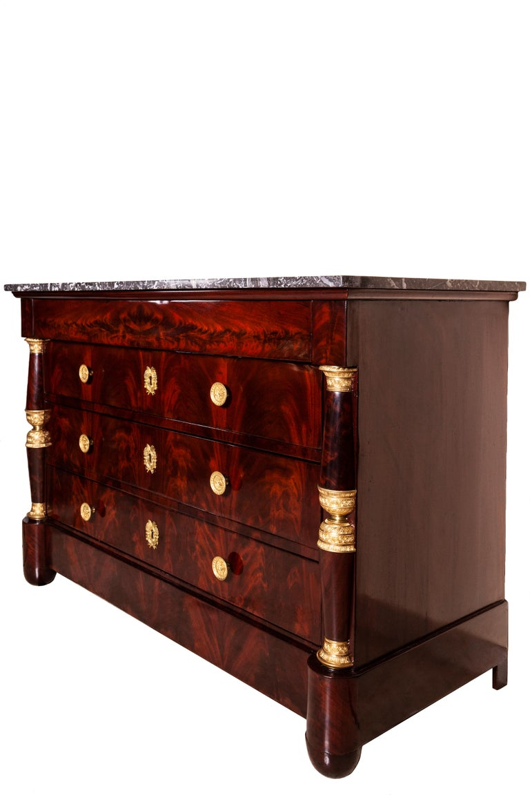 19th century, French mahogany commode On the top, it has a veined gray marble.  Cabinet with beautiful proportions with drawers in flamed mahogany. On the sides, there are two columns embellished with gilded bronze capitals.  Restored and in