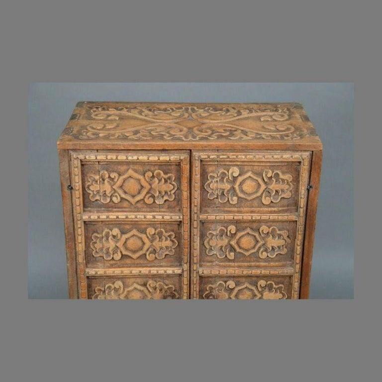 This extraordinary carved Indonesian two door cabinet will make a beautiful addition to your home. Made of teak with incredible relief carved decoration on all surfaces, it has wonderful small proportions which makes it a great fit for smaller