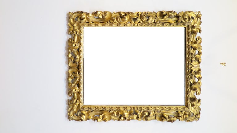 Italian 19thcentury baroque hand carved mirror. Hand carved of solid wood from the middle 19th century having Gesso and gold leaf. Acanthus leaf carving adorns the mirror frame. Glass and mirror affect are clear with good reflection. Some age spots