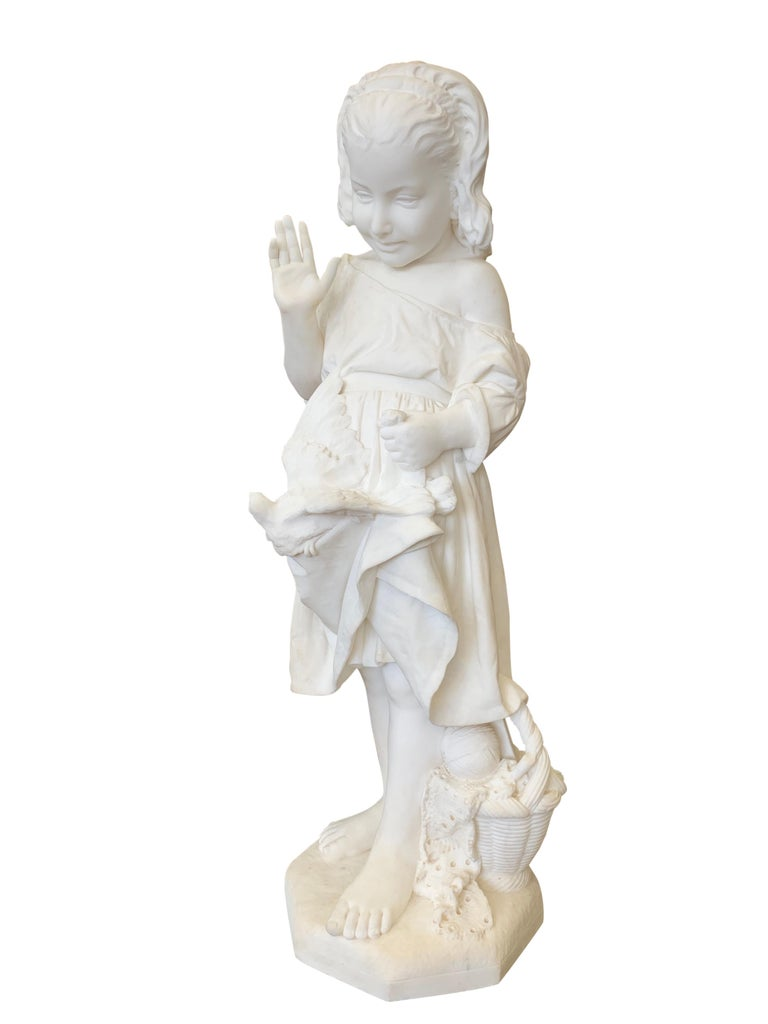 A lovely 19th century carved Carrara marble figure of a young girl waving  her right hand as a dove rests on her dress, she is standing aside a basket with a ball of string and a garment, by Emanuele Caroni.  Signed: E. Caroni, Firenze  Dated