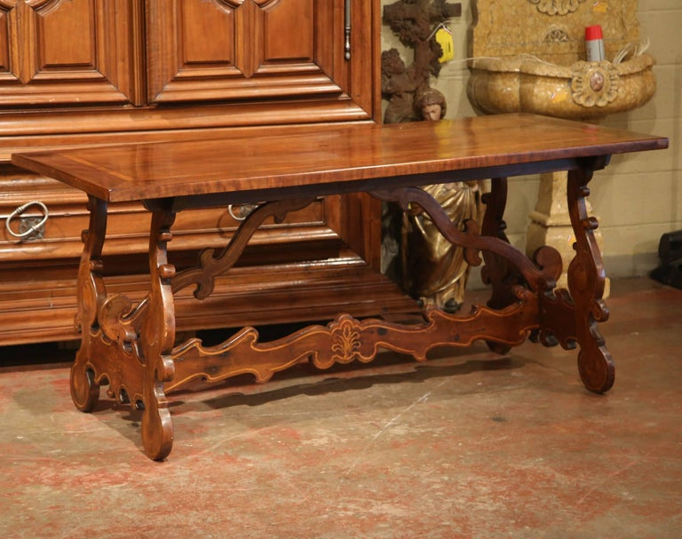 This elegant, antique fruit wood dining room table was crafted in Italy, circa 1830. The intricate table features a solid top made from a single walnut plank and embellished with a decorative inlay cherry band around the perimeter. The base has two