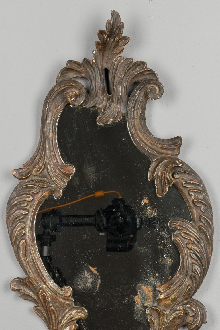 A small 19th century Italian Baroque style mirror with decorative carved wood frame. Original mirror with old silvering. Nice patina.