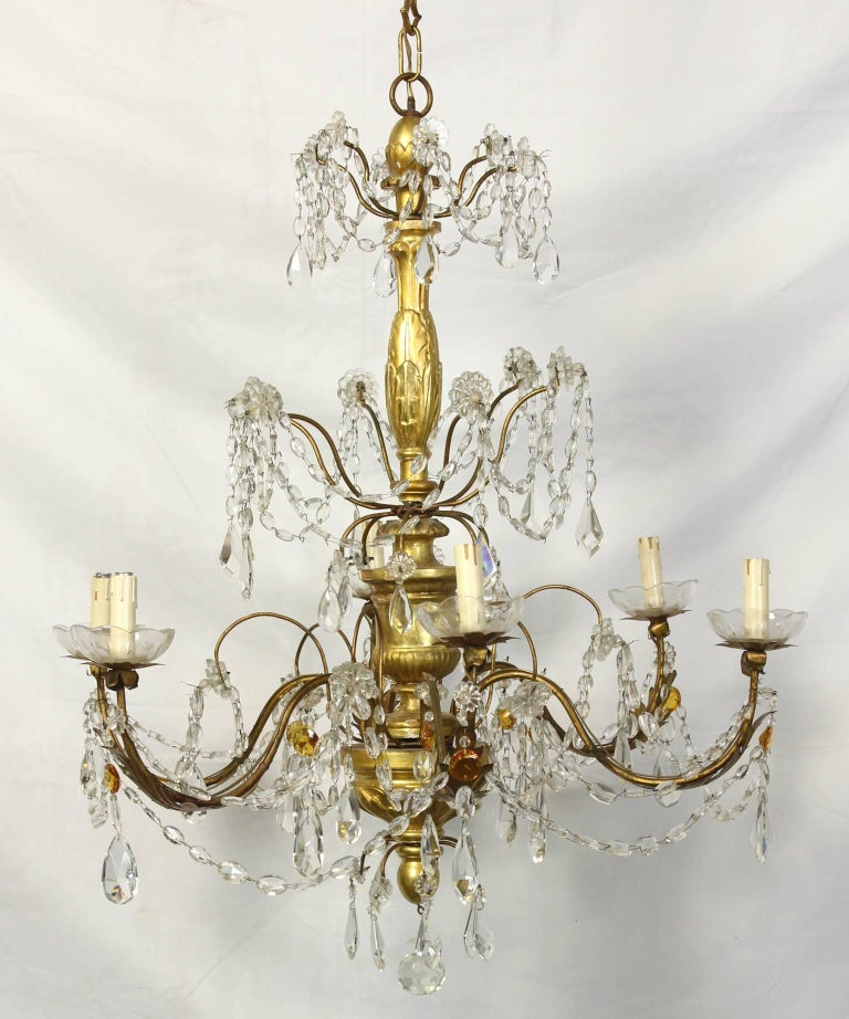 An Italian giltwood and crystal six-light chandelier dating from the early 19th century. The chandelier features a central giltwood staff adorned with gilt iron arms draped with swags of clear and amber crystals.