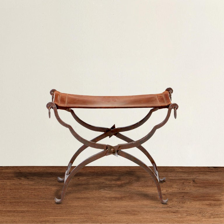 An incredible 19th century Italian wrought iron folding Curule stool with a hand-stitched saddle leather seat, rings on the ends, and decorative stars where the legs cross on both sides. Curule seats were designed by early Romans and was seen as a