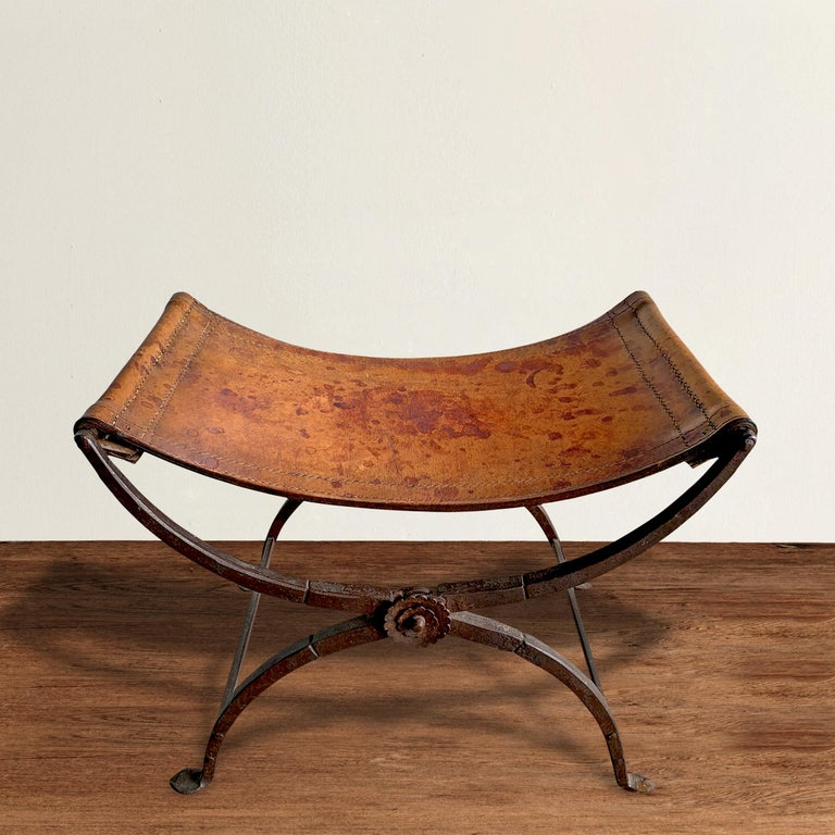 A striking 19th century Italian wrought iron folding Curule stool with a handstitched saddle leather seat and decorative floral rosettes on both sides where the legs cross. Curule seats were designed by early Romans and were seen as a symbol of
