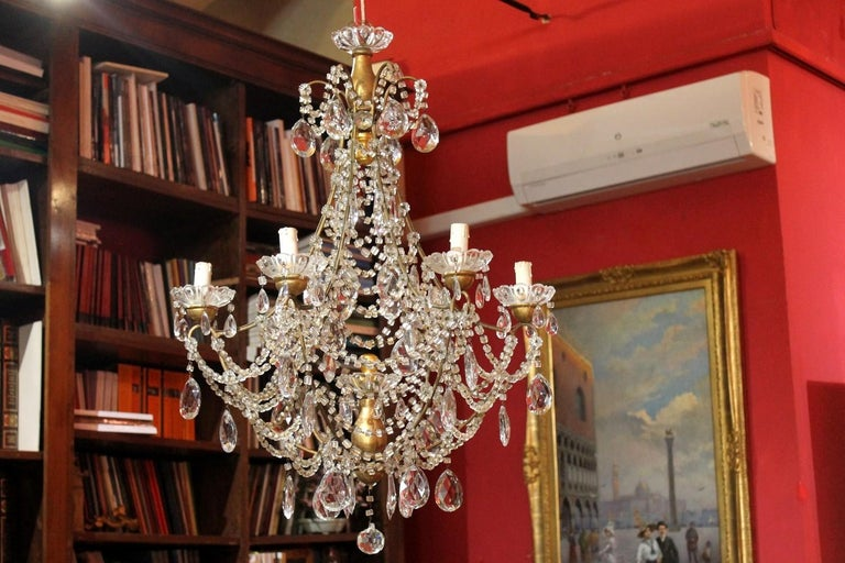 Sparkling and shiny this Louis XVI style six arms chandelier manufactured in Florence in early 19th century is the attractive eye-catching lighting pendant. The gilt casted iron basket frame has a pear-shaped structure completely adorned with
