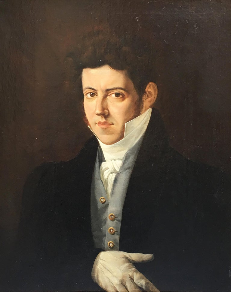 A charming Italian Empire oil on canvas painting depicting the portrait of a young gentleman. The painting presents an elegant giltwood frame.