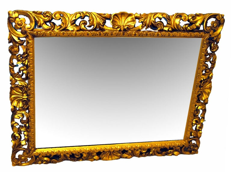 A very attractive mid-19th century giltwood wall mirror of Florentine design having superbly carved cushion frame enclosing mirror plate  (This delightful mirror would brighten up any room. The carving is superbly executed and remains in