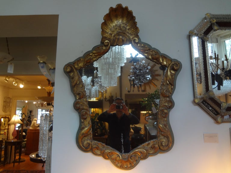 Stunning early 19th century Italian giltwood mirror with shell design. Well detailed with fabulous time worn patina to the gilt. This Italian giltwood mirror would work well in a variety of interiors and would be perfect in a powder bath.