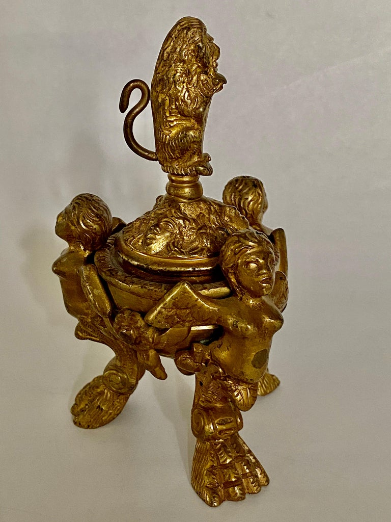 After a 16th century Venetian design, winged putti with taloned legs support a turned bronze inkwell covered with a lid decorated with masks and garlands, surmounted by a lion holding a shield.
