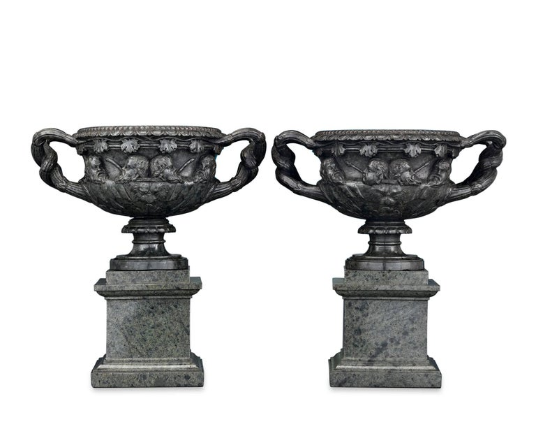 This remarkable pair of carved green serpentine marble vases were modeled after the legendary Warwick vase. Found at the Roman Emperor Hadrian's villa in 1770 and subsequently held in the collection of the Earl of Warwick, the vase remains one of