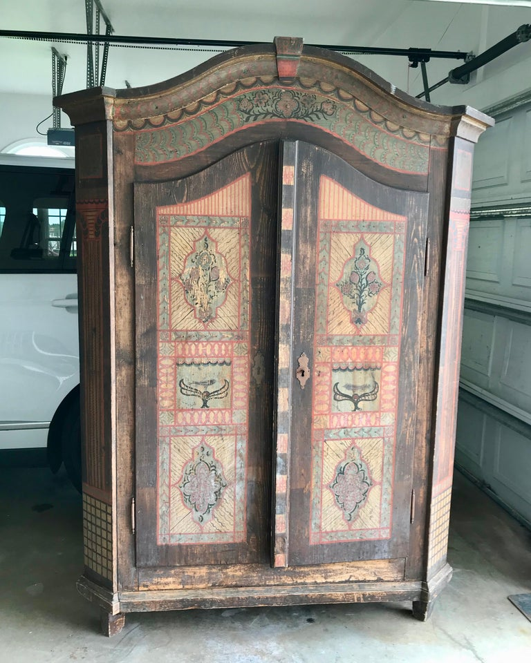 The cabinet is hand painted with double doors. Northern Italian (Alpine) origin. The cabinet is fitted with shelves. The cabinet is dated 1820 on its crown.