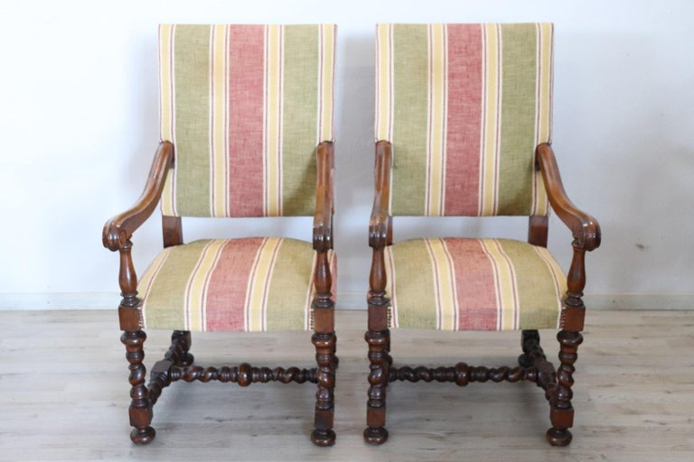 Italian Louis XIV style pair of armchairs very comfortable. Completely in slide walnut wood with refined turned decoration in the legs. The seat padding with defects, it would be necessary to restore. Fabric and wood in perfect condition.