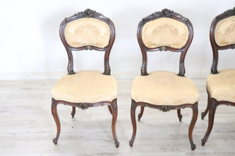 Series of refined Italian Louis XV style four chairs in solid walnut wood. The walnut wood is carved with floral decorations. The legs are very elegant. The seat is wide and comfortable with yellow cloth. The chairs are used good conditions. Please