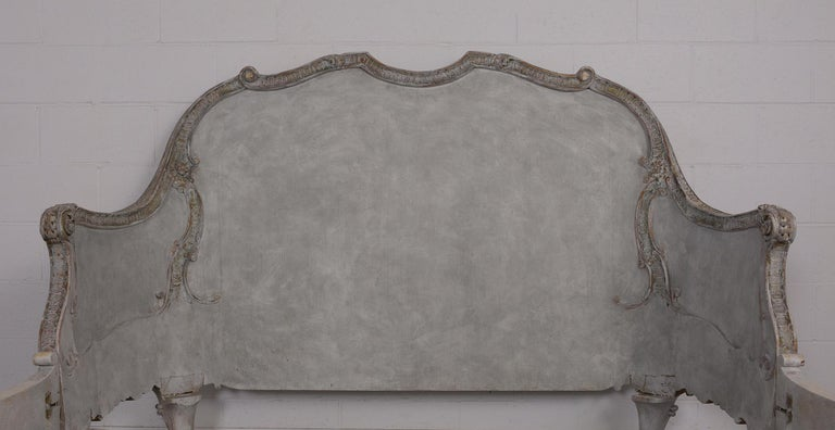This late 19th century Italian Louis XV style bed frame fits a Queen sized mattress. It has a solid wood frame that is painted a pale light blue and grey color combination with a distressed finish. It features hand carved floral details on the