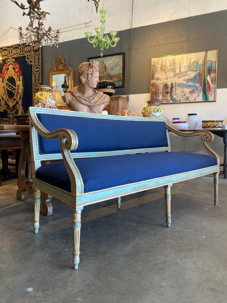 """Italian Louis XVI style hall bench settee with sweeping arms, and 6 fluted legs. Antique beige and soft blue 2-tone patina highlighted by gold gilt details, Tuscany, circa 1820.  Professionally reupholstered.  Blue fabric.  Measures: 65.75"""" width"""