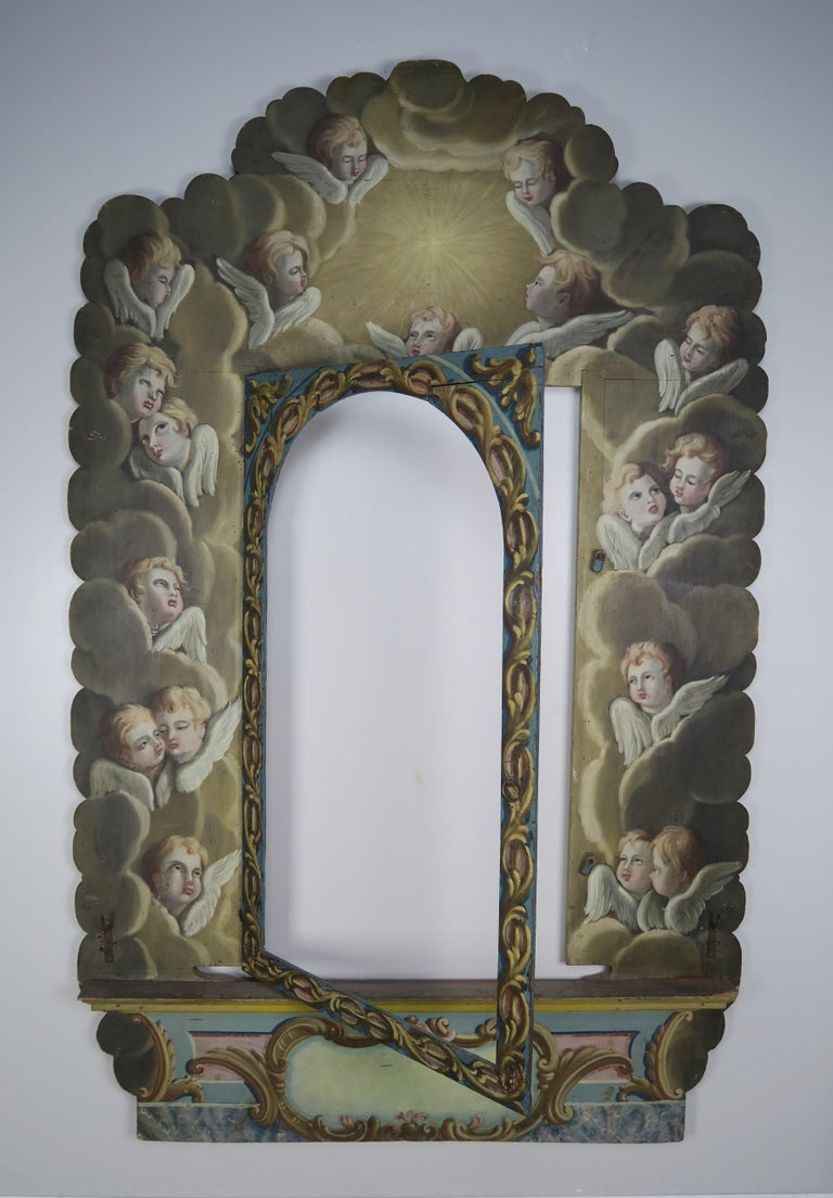 Incredible hand painted frame with cherub faces intricately painted throughout floating throughout clouds as though they are ascending towards heaven.