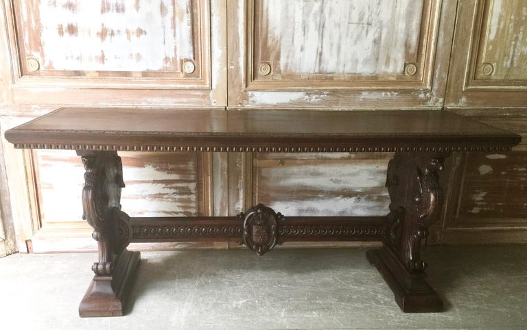 19th century extravagantly-carved Italian Renaissance-Revival library table in walnut witch carved trestle ends with griffins, female busts, northwind faces, shields, scrolls and crowns connected by a carved stretcher with the crest under the