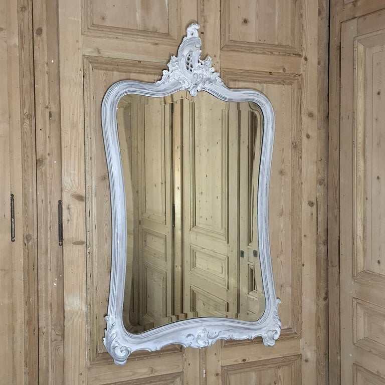 19th century Italian Rococo painted mirror features a distressed painted finish and its original beveled mirror for a delightfully light and airy effect while bouncing ambient light around the room. Hand-carved from the cartouche to the elaborately